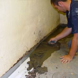A basement waterproofer installing a perimeter drain system in Elk River